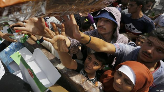 Syrian refugees and other migrants struggle to get dry food during aid distribution by workers of the Kos municipality on the Greek island of Kos 14 August 2015.