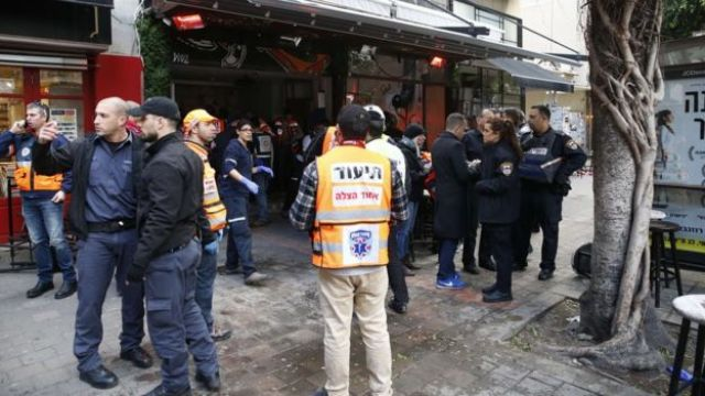 Members of the Israeli security forces stand outside a pub following an attack by an unidentified gunman who opened fire killing two people and wounding five others in the Israeli city of Tel Aviv on January 1, 2016,