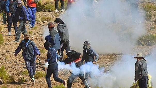 Mineros lanzando de regreso un tubo de gas lacrimógeno
