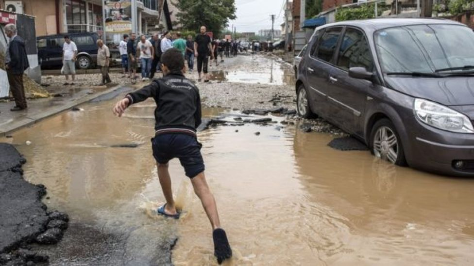 boy running through floodwater next to abandoned car in busy street