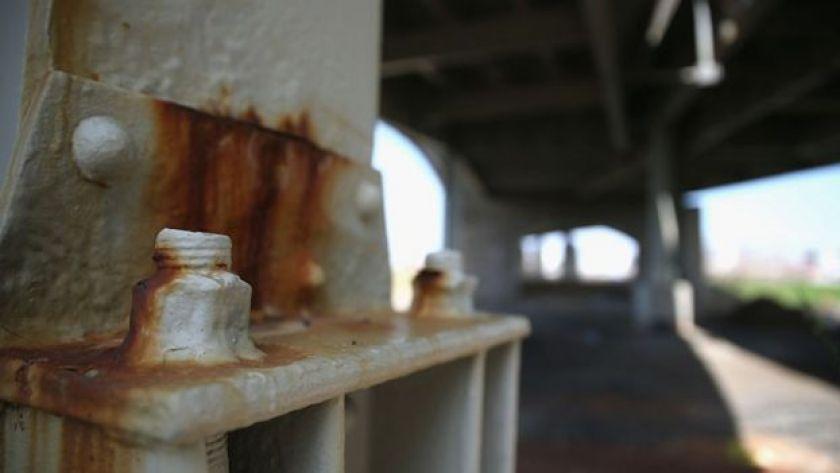 A bolt under a bridge is rusting.