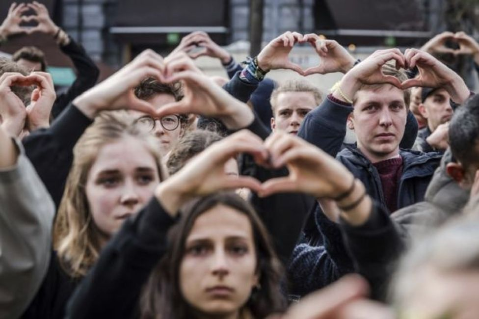 People make the shape of a heart with their hands as they stand for a moment of silence at the Bourse during the one-year anniversary for Brussels attacks victims in Brussels, 22 March