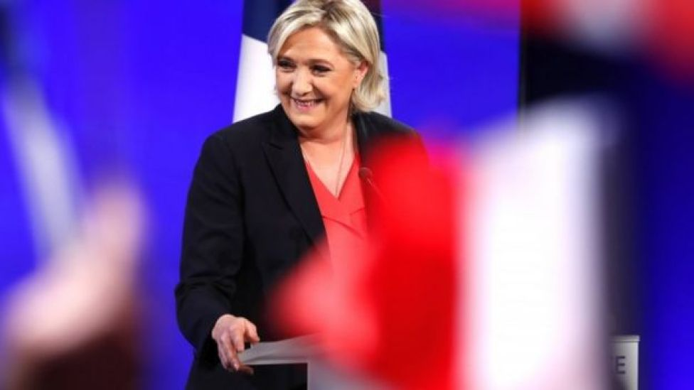 Marine Le Pen delivers a speech on stage after losing the French presidential run-off