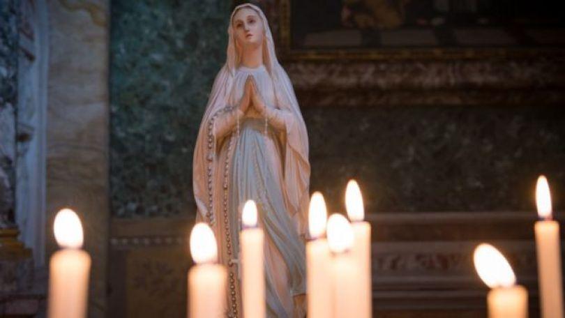 Estátua de Maria Madalena ao lado de velas