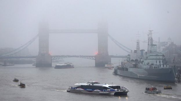 Boats passing under Tower Bridge in London, surrounded by fog