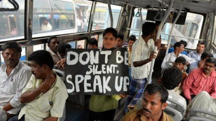 فتاة تحمل لافتة تطالب النساء بعدم السكوت عن التحرش