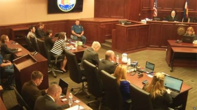 James Holmes (top left in a tan shirt) watches as Judge Carlos Samour (top right) prepares to reveal the jury's decision