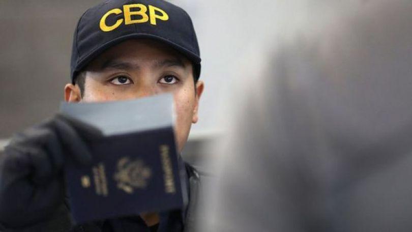 Un funcionario de Migración verifica un pasaporte en un aeropuerto de Estados Unidos.