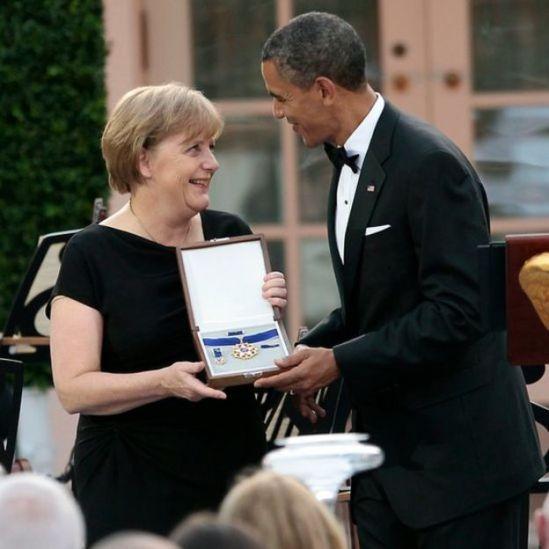 Angela Merkel junto a Barack Obama, ambos sonriendo.