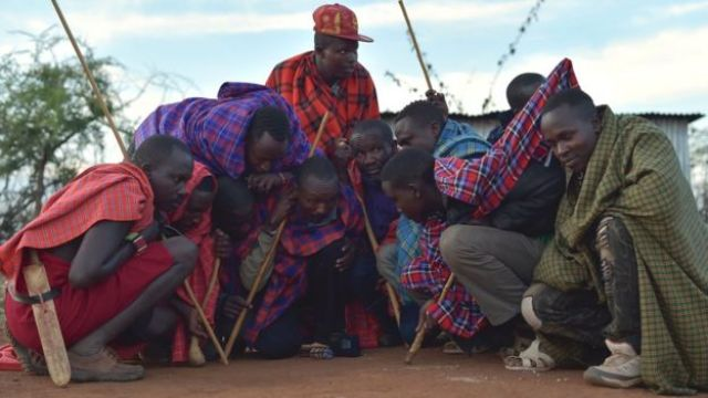 A group of Maasai men crouching around a radio near Saikeri, Kenya - Tuesday 8 November 2016