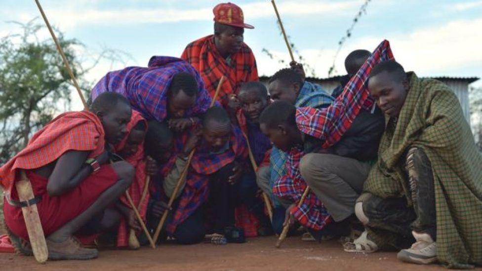 A group of Maasai men crouching around a radio near Saikeri, Kenya - Tuesday 8 November 2016