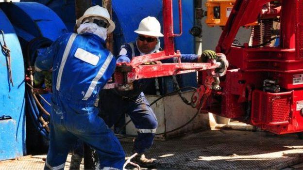 Homens trabalhando em área de exploração de petróleo