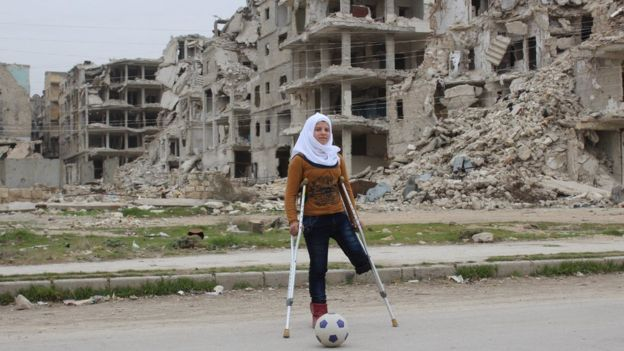 Image of Saja, a Syrian child missing a leg, playing football in front of bombed buildings