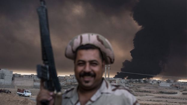 An Iraqi soldier holds a rifle as smoke billows from the Qayyarah area,