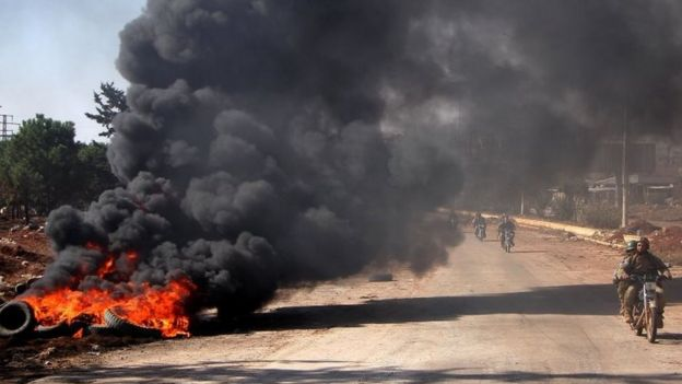 Rebel fighters from the Jaish al-Fatah (or Army of Conquest) brigades drive past burning tyres at an entrance to Aleppo, in the south-western frontline near the neighbourhood of Dahiyet al-Assad (03 November 2016)