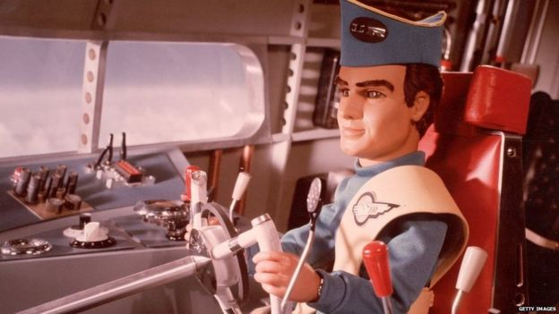 A marionette pilot in uniform steers a vehicle