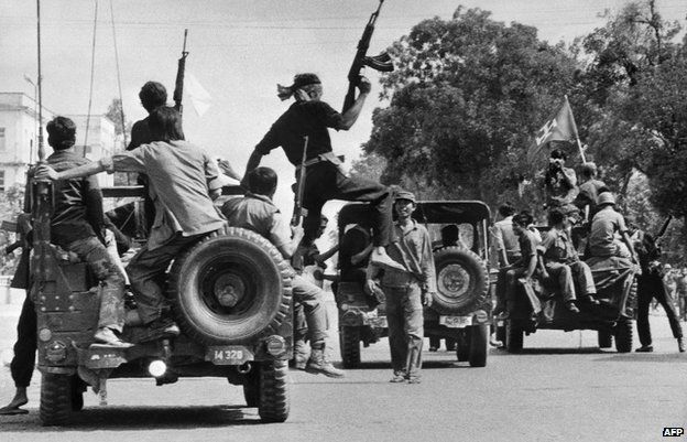 Khmer Rouge guerrilla soldiers drive through a street in Phnom Penh on 7 April 1975 - the day Cambodia fell under the control of the Communist Khmer Rouge's forces.