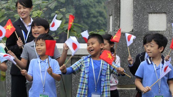Nhiều trẻ em đứng đón đoàn quan khách tại Hà Nội.