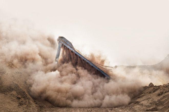 Un edificio cae en una nube de polvo en Sokhna, Egipto.