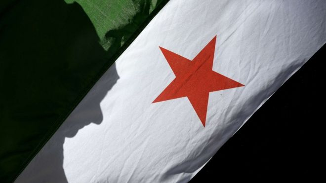 """A woman""""s shadow is cast onto close up Syrian Flag"""