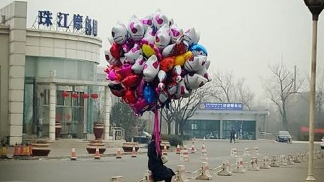 A man sits alone holding a bunch of balloons