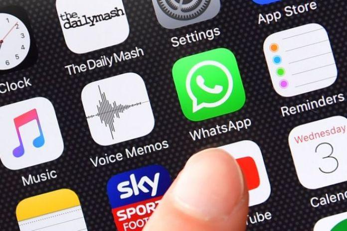 Dedo señala el icono del WhatsApp en la pantalla de un celular.