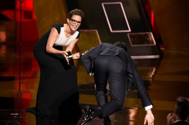Tina Fey (left), prepares to present Jon Hamm with his award