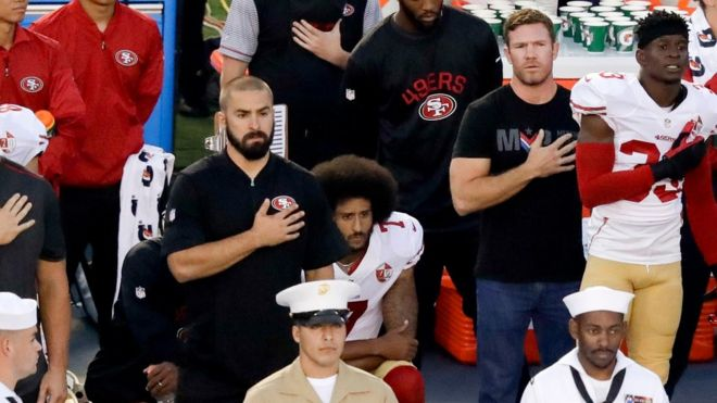 (San Francisco 49ers quarterback Colin Kaepernick, middle, kneels during the US national anthem, via BBC)