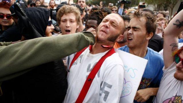 Una persona no identificada le da un puñetazo a un joven que lleva una camiseta con figuras de esvásticas.