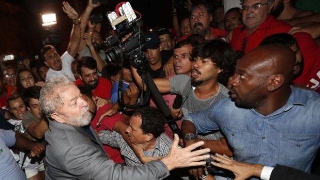 Lula saliendo del sindicato metalúrgico entre seguidores y periodistas.