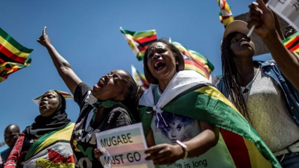 """This file photo taken on November 18, 2017 shows supporters of Tajamuka Sesijikisile SA, The African Democrats Opposition Party, the Zimbabwe Communist Party, the Zimbabwe Diaspora Coalition and other groups attending a rally at the Union Buildings in Pretoria, South Africa, to call for the resignation of Zimbabwe""""s President."""