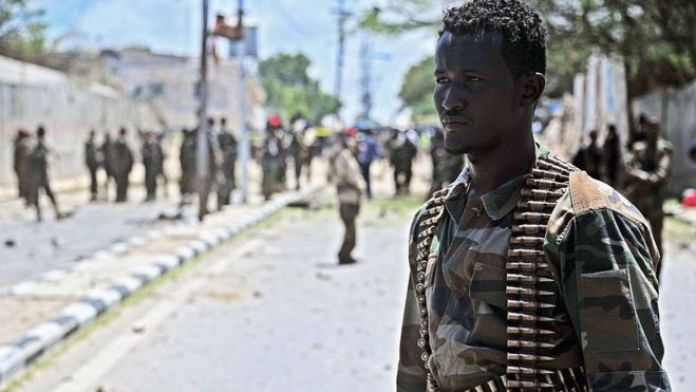 A Somalian soldier at the scene of a suicide car bomb blast in Mogadishu on August 30, 2016