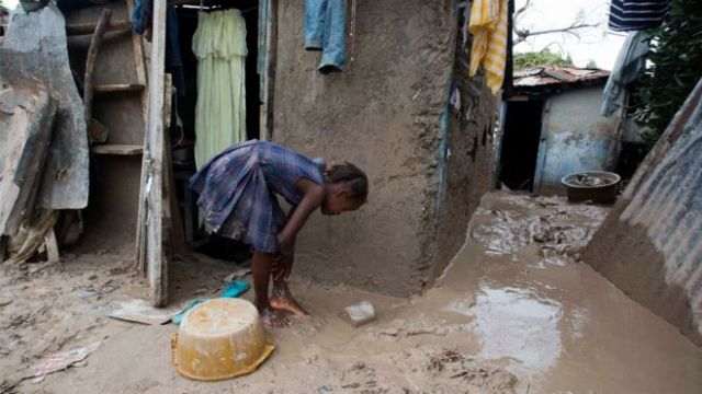 A girl washes mud from her feet after Hurricane Matthew passed in Les Cayes, Haiti