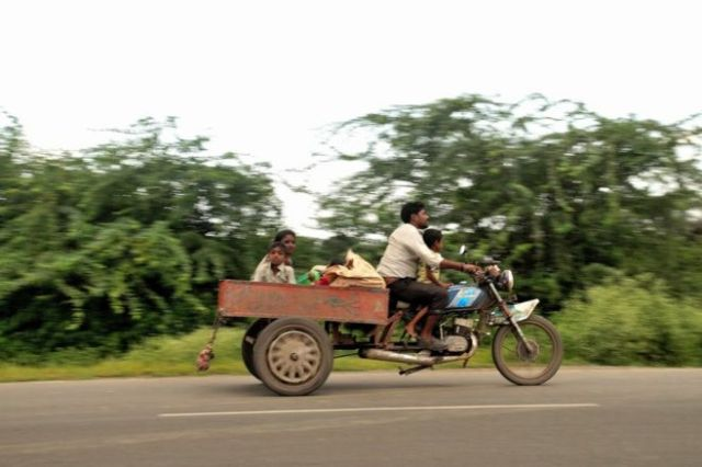 இருசக்கர வாகனத்தில் குடும்பத்துடன் செல்லும் நபர்