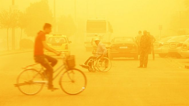 A man rides a bicycle through a sandstorm in Homs, Syria September 7, 2015