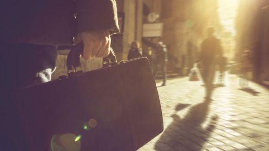 Homem caminha pela rua segurando uma pasta