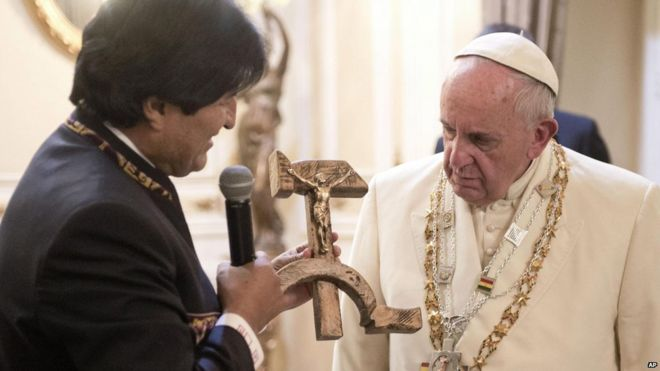 Pope Francis is presented with a gift of a hammer and sickle-shaped crucifix