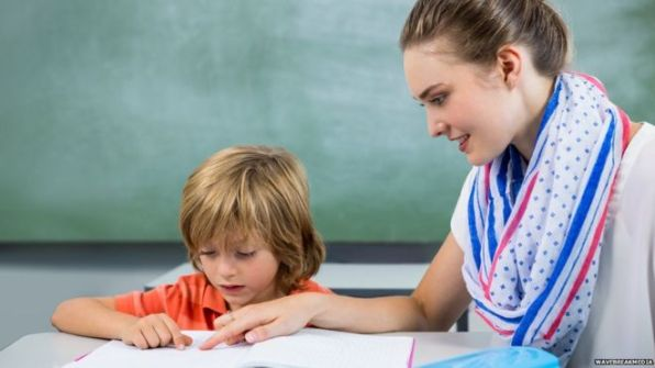 Child reading with teaching assistant