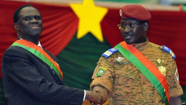Interim President of Burkina Faso Michel Kafando (L) and Prime Minister Lt Col Isaac Zida (R) shake hands during Mr Kafando's inauguration ceremony on 21 November 2014 in Ouagadougou