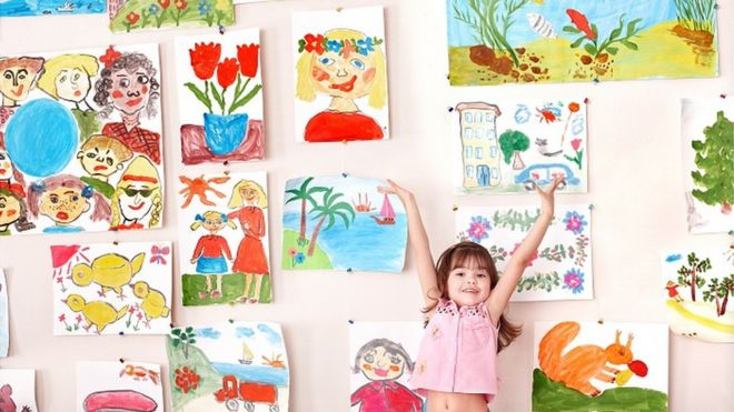 Child showing off artworks
