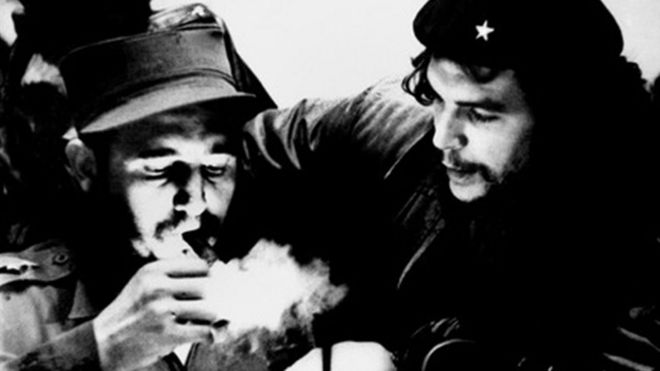 Fidel Castro acende charuto enquanto ouve Che Guevara em foto tirada na década de 1960