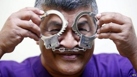 """Malaysian political cartoonist Zulkiflee Anwar Haque, or """"Zunar"""", reacts with mock handcuffs during his case at Duta Court, in Kuala Lumpur, 03 April 2015"""