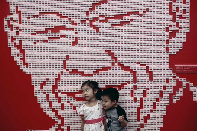 Two young children pose for a photograph against a mural made out of nearly 5,000 Singapore country erasers forming the likeness of Mr Lee Kuan Yew, during a tribute event in Singapore, 20 March 2016.