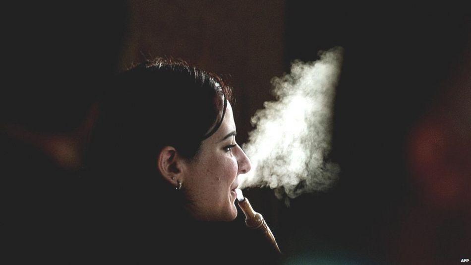A woman smokes Shisha at a cafe in Dubai on May 31, 2008.