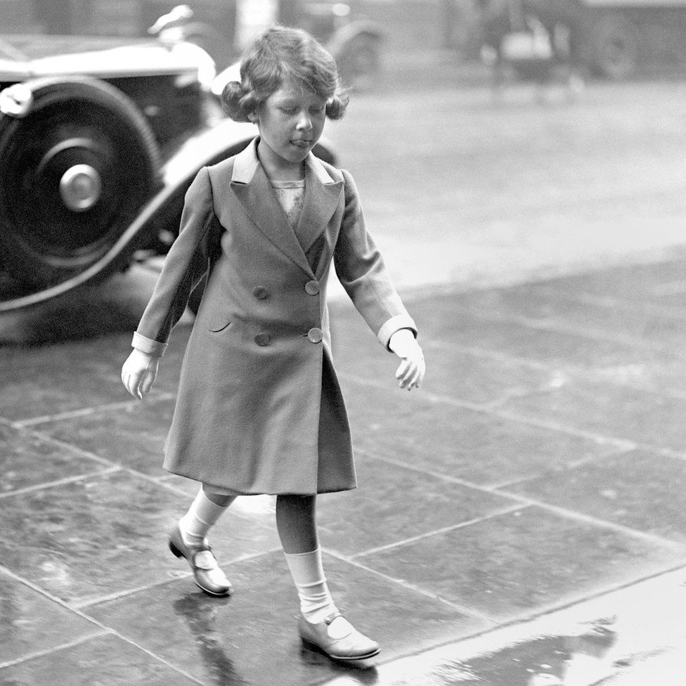 Princess Elizabeth walking through the rain on her arrival home