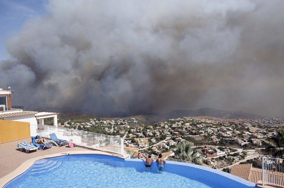 Zwei Männer schauen Sie sich ein Lauffeuer aus einem Swimmingpool, wie es in der Nähe Benitachell Dorf, im Osten Spaniens brennt,