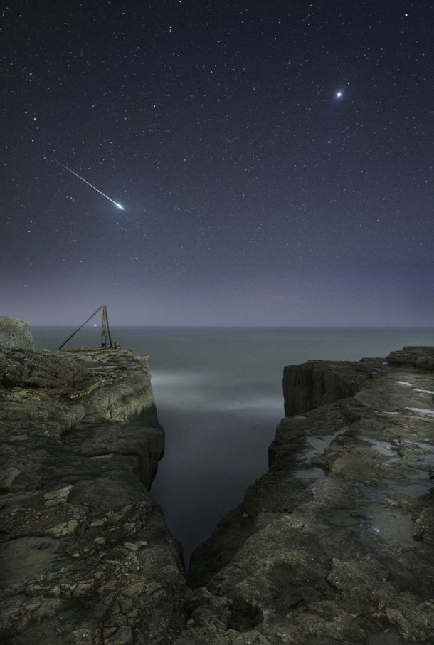 A shooting star flashes across the sky over the craggy landscape