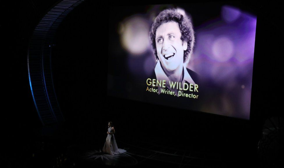 "Sara Bareilles performs during the ""In Memoriam"" segment with an image of the late Gene Wilde"