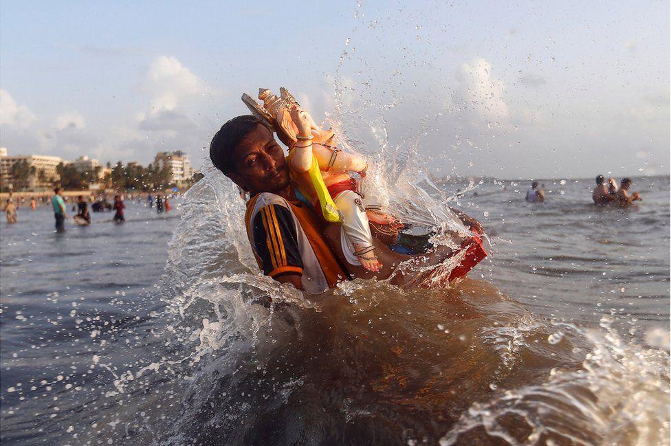 Ein Anhänger trägt ein Idol des Hindu-Gottes Ganesh, der Gott des Wohlstands, in das Arabische Meer am zweiten Tag von Ganesh Chaturthi Festival in Mumbai