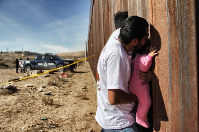 """A man holds a baby at the border wall between Mexico and United States, during the """"Keep our dream alive"""" event, in Ciudad Juarez, Chihuahua state, Mexico on 10 December 2017."""